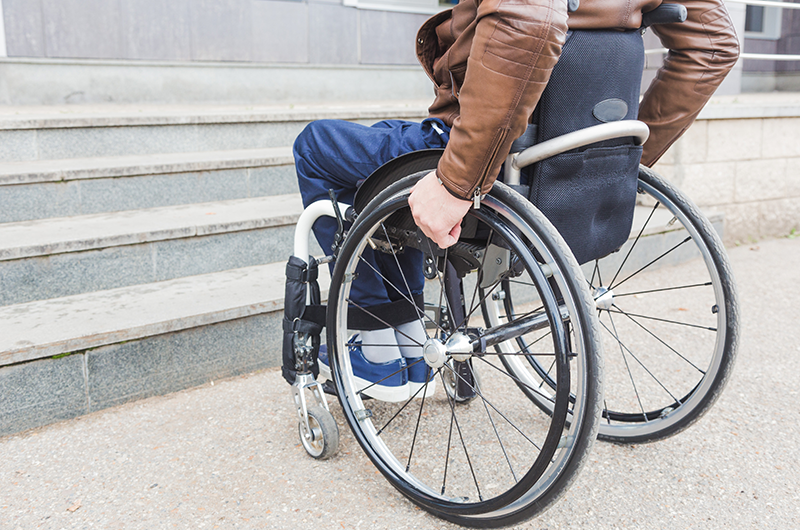 man in wheelchair in a city at the base of stairs