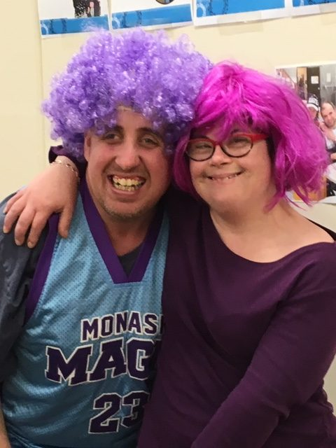 Two young people wearing colourful wigs.